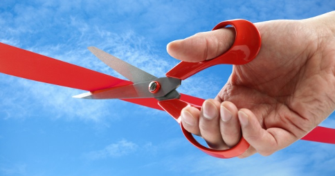Right hand holding open scissors over a line of red tape