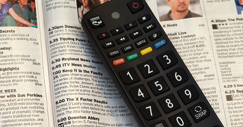 Television remote control resting on printed TV guide