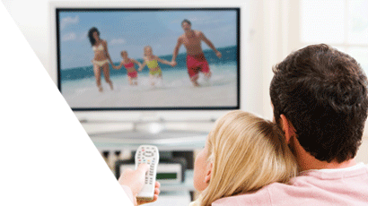 Young couple seated in front of a TV, woman pointing remote control at screen